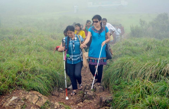 Two blind participants hiking on mountain and there are other people behind in a misty environment