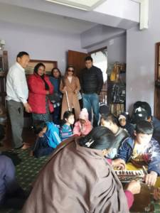 Sristi and her team standing in a room where disabled children are sitting and some are playing musical instruments