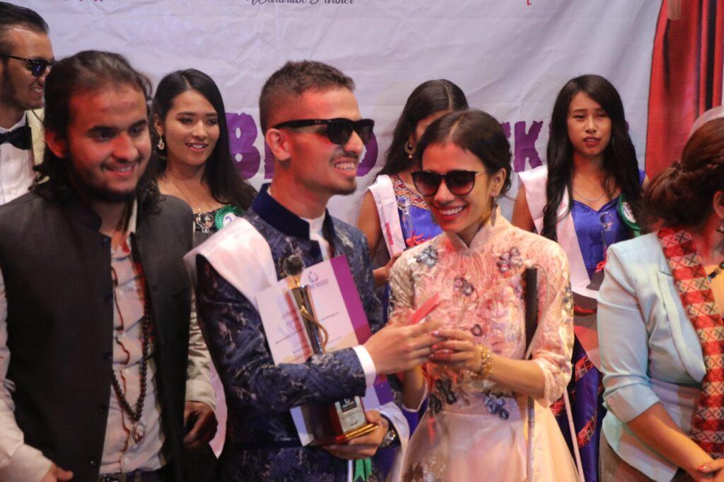 Sristi KC providing award for Mr Blind Rocker
